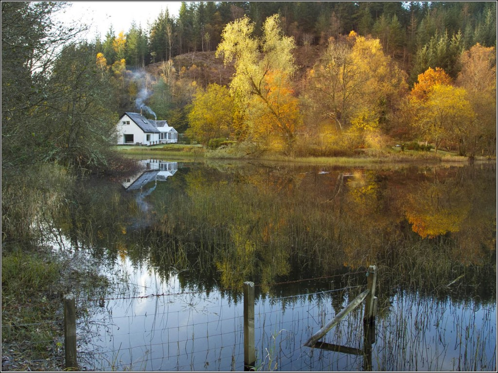 refelction of white cottage on a loch
