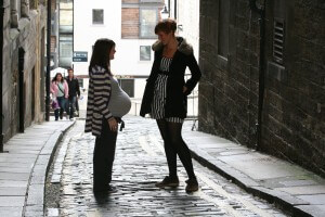 Two women chat in cobbled street