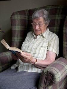 elderly woman chair reading book